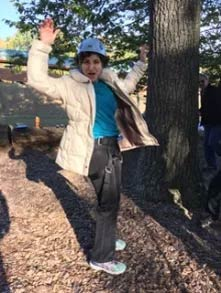 woman holding hands up by tree